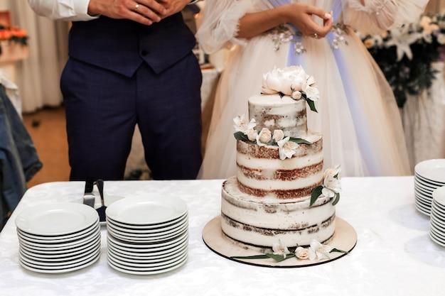Eine schöne hochzeitstorte steht auf dem tisch neben braut und bräutigam