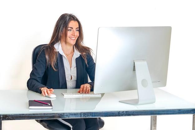 Eine schöne hübsche lächelnde sekretärin schreibt glücklich und fröhlich auf ihrem computer im büro