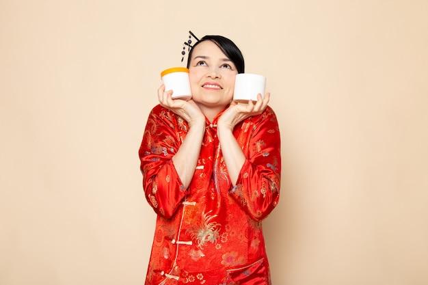 Eine schöne japanische geisha der vorderansicht im traditionellen roten japanischen kleid mit den haarstäbchen, die das halten von cremedosen auf der cremefarbenen hintergrundzeremonie japan posierend halten