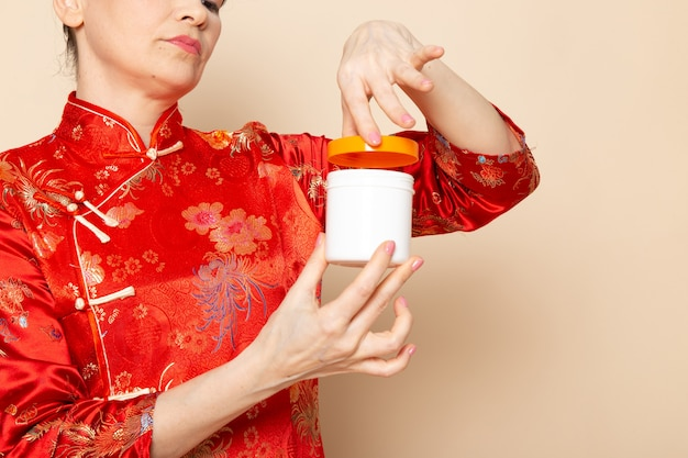 Eine schöne japanische geisha der vorderansicht im traditionellen roten japanischen kleid mit den haarstäbchen, die haltecremedose auf der cremehintergrundzeremonie japan aufwerfen
