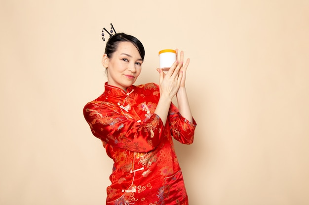 Eine schöne japanische geisha der vorderansicht im traditionellen roten japanischen kleid mit den haarstangen, die haltecreme darstellen, kann auf der cremehintergrundzeremonie japan lächeln