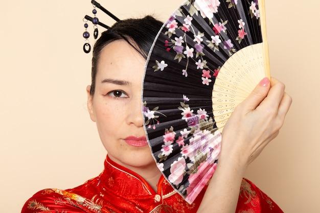 Eine schöne japanische geisha der vorderansicht im traditionellen roten japanischen kleid mit den haarstöcken, die das falten des faltfächers elegant auf der cremefarbenen hintergrundzeremonie japan aufwerfen