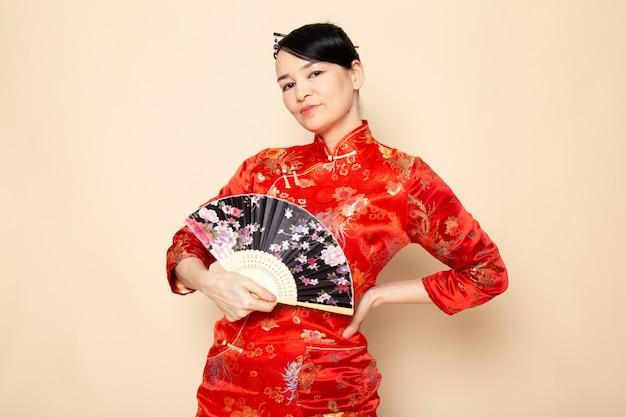 Eine schöne japanische geisha der vorderansicht im traditionellen roten japanischen kleid mit den haarstöcken, die das falten des faltfächers lächelnd auf der cremehintergrundzeremonie japan aufwerfen