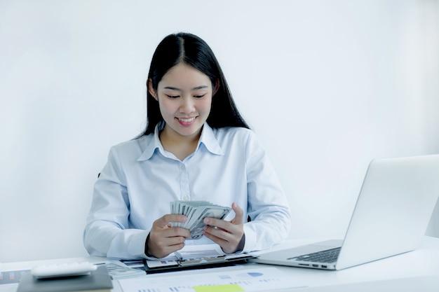 Eine schöne junge asiatische schöne frau mit langen haaren, die eine dollarnote halten, verwenden einen laptop, der ein konto für die zahlung von steuer auf dem weißen schreibtisch macht, der im heimbüro arbeitet.