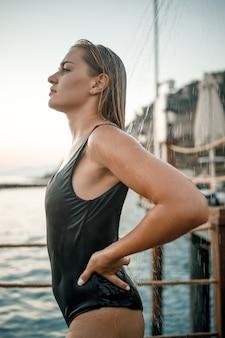 Eine schöne junge attraktive frau in einem schwarzen badeanzug mit einer schönen figur steht unter einer sommerdusche auf dem pier am meer. sie genießt ihren urlaub. selektiver fokus