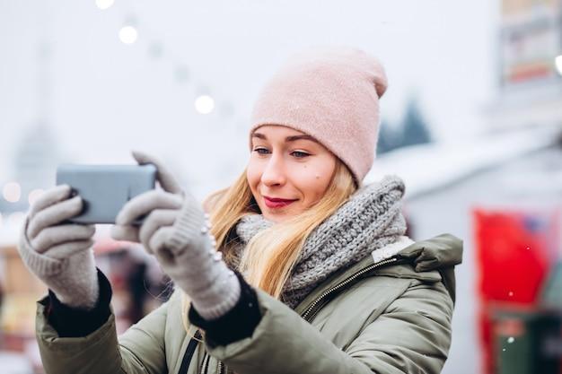 Eine schöne junge blonde frau, die in ein telefon für ein bild auf dem weihnachtsmarkt lächelt