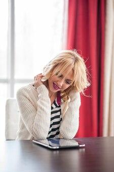 Eine schöne junge blonde frau, die mit einem laptop am tisch sitzt.