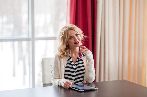 Eine schöne junge blonde frau, die mit einem laptop am tisch sitzt