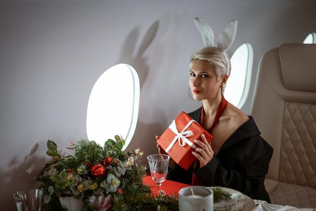 Eine schöne junge blonde frau mit kurzen haaren und hasenohren sitzt in einem privatjet mit einem ...