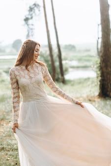 Eine schöne junge braut im weißen kleid in einem wald