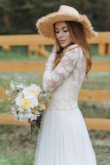 Eine schöne junge braut mit einem strauß gänseblümchen auf einem feld