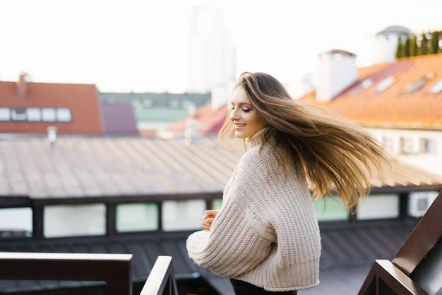 Eine schöne junge brünette lächelt breit und ihr haar entwickelt sich im wind, während sie sich dreht.
