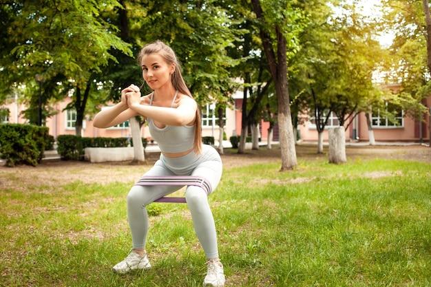 Eine schöne junge frau beschäftigt sich mit einem sportplatz im park. fitness, training, outdoor. sonnenblendung, stretchgummi, sportgeräte. trainierter muskulöser körper und po. mädchen lächelt, glücklich