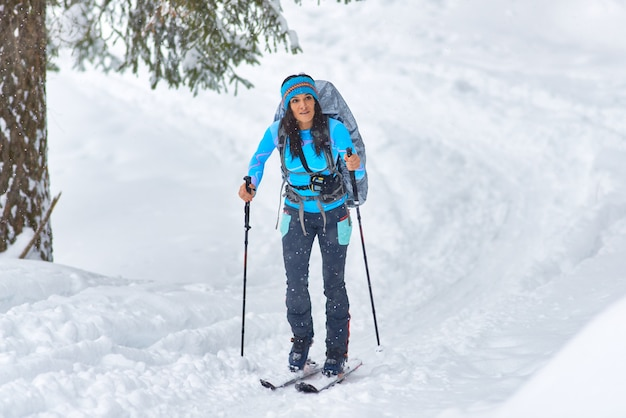Eine schöne junge frau, die allein das wandern skifahren übt