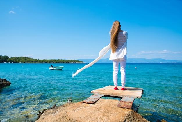Eine schöne junge frau, die den wind und das klima im sommer am meer genießt.