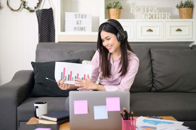 Eine schöne junge frau, die ein headset trägt, macht eine videokonferenz über einen computer zu hause, ein geschäftstechnologiekonzept.