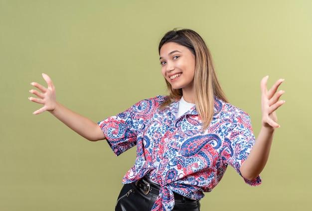 Eine schöne junge frau, die ein hemd mit paisley-aufdruck trägt, öffnet die hände zum umarmen, während sie auf eine grüne wand schaut