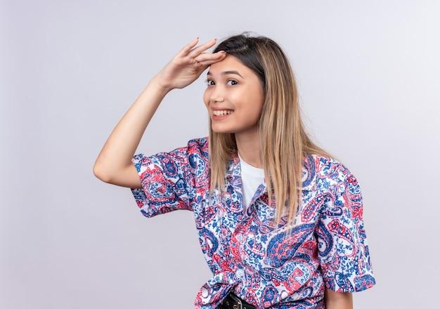 Eine schöne junge frau, die ein mit paisley bedrucktes hemd trägt, das weit weg schaut und nach etwas auf einer weißen wand sucht