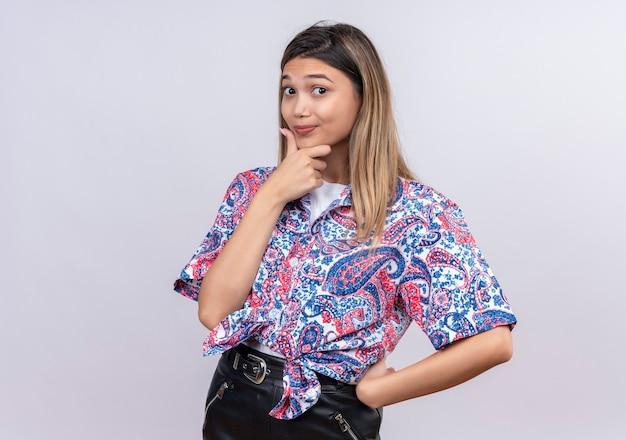 Eine schöne junge frau, die ein mit paisley bedrucktes hemd trägt und ihre hand am kinn hält, während sie auf eine weiße wand schaut