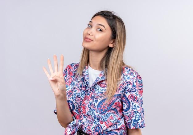 Eine schöne junge frau, die ein paisley-bedrucktes hemd trägt, das nummer vier mit den fingern zeigt, während sie auf eine weiße wand schaut