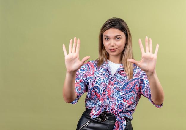 Eine schöne junge frau, die ein paisley-bedrucktes hemd trägt, das nummer zehn zeigt