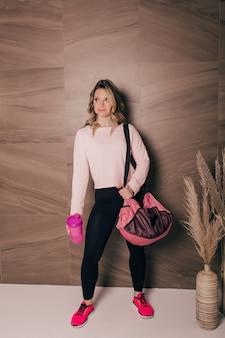 Eine schöne junge frau, die eine sporttasche und eine wasserflasche hält, schaut in die kamera