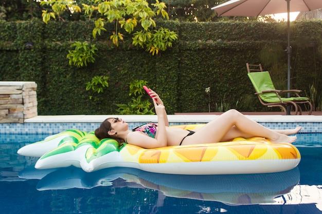 Eine schöne junge frau, die ihr smartphone benutzt, das auf ihrem schwimmer im pool liegt.