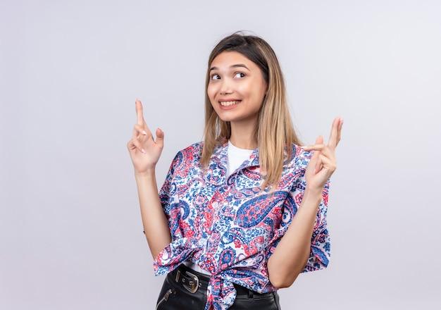 Eine schöne junge frau, die paisley-bedrucktes hemd trägt, das finger als glücks- oder hoffnungsgeste auf einer weißen wand kreuzt