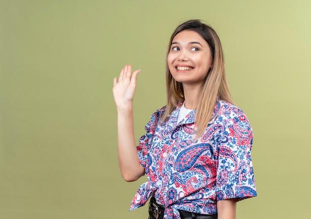Eine schöne junge frau, die paisley-bedrucktes hemd trägt, das hand winkt und auf wiedersehen sagt, während seite auf einer grünen wand schaut