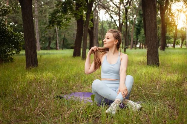Eine schöne junge frau, die yoga im park auf dem gras macht. gymnastikmatte, sportgeräte. training, im freien. gesunder lebensstil, gewichtsverlust, fitness. trainierter muskulöser körper. frische luft. porträt