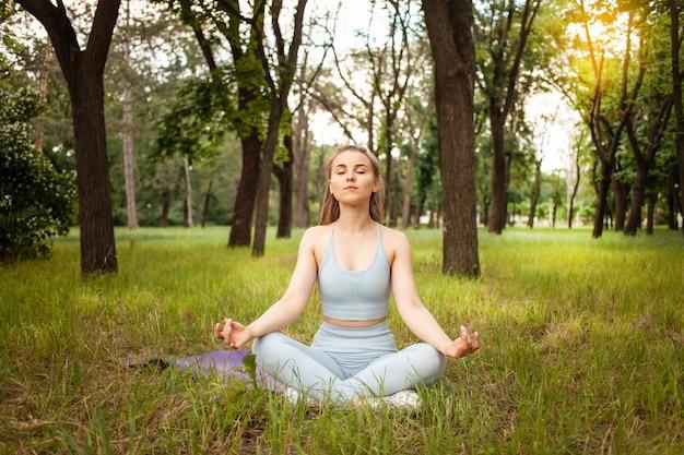 Eine schöne junge frau, die yoga im park auf dem gras macht. gymnastikmatte, sportgeräte. training, im freien. gesunder lebensstil, gewichtsverlust, fitness. trainierter muskulöser körper. frische luft. sonniger glanz