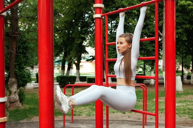 Eine schöne junge frau führt eine übung an der frischen luft durch. sportplatz, park. fitness trainierter körper. yoga, im freien. eine gesunde lebensweise. drücken sie, das mädchen hängt in den armen, die treppe. trainieren