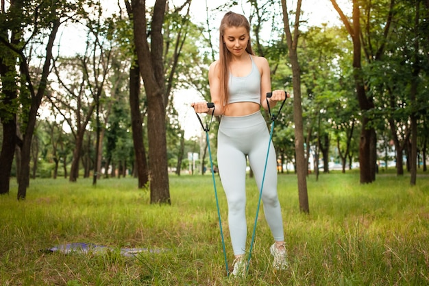 Eine schöne junge frau führt eine übung im freien durch. gras, park, sporttraining. fitness. ein expander. sportgeräte, sonnenuntergang. ein gesunder lebensstil, trainierter muskulöser körper.