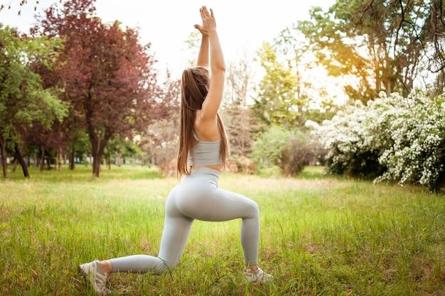 Eine schöne junge frau führt übungen im park, auf dem gras, im freien durch. yoga, fitness, muskulöser körper. sonniger glanz. eine gesunde lebensweise. training, wald in der stadt.