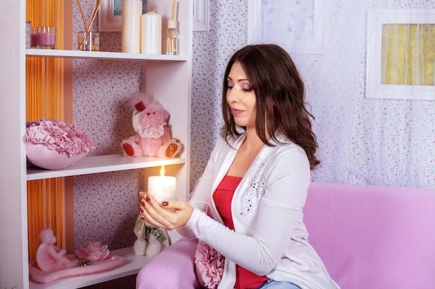 Eine schöne junge frau hält eine kerze in einem rosa raum.