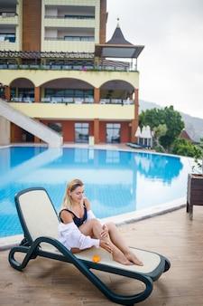 Eine schöne junge frau in badeanzug und weißem hemd sitzt auf einer sonnenliege am pool und reibt ihren körper mit sonnencreme ein. sommerliche hautpflege, schutz vor hautverbrennungen