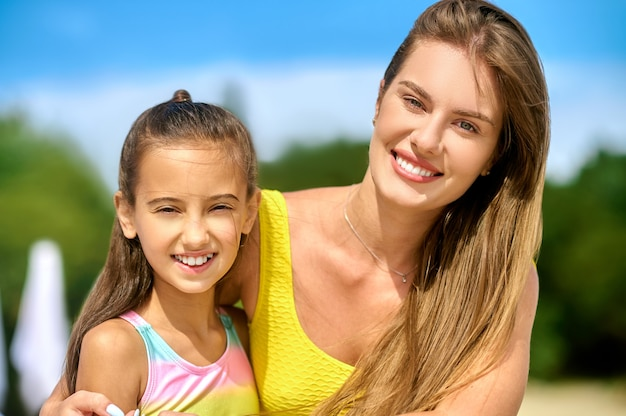 Eine schöne junge frau in einem gelben badeanzug und ihre tochter am strand