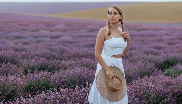 Eine schöne junge frau in einem weißen kleid mit hut geht durch ein lavendelfeld