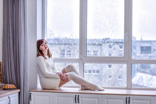 Eine schöne junge frau in einem weißen strickpulloverkleid und langen leggings sitzt auf einer breiten fensterbank am fenster. blick in die ferne, trauriges konzept der einsamkeit. speicherplatz kopieren. weiße innenräume
