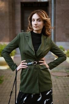 Eine schöne junge frau in stilvollen kleidern mit haaren und make-up posiert tagsüber für die kamera auf der straße.
