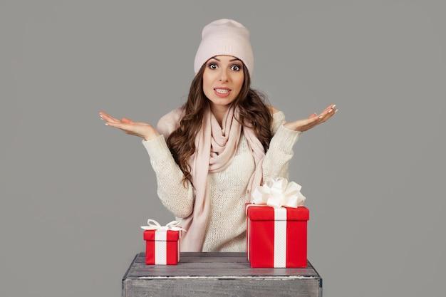 Eine schöne junge frau in winterkleidung steht nachdenklich und zögernd vor der wahl eines kleinen oder großen geschenks für neujahr und weihnachten. das mädchen entscheidet, welches geschenk es wählt.