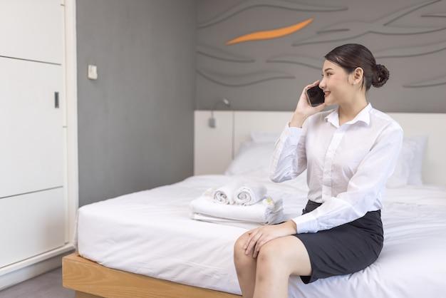 Eine schöne junge frau liegt auf einem bett in einem weißen bademantel in einem hotel