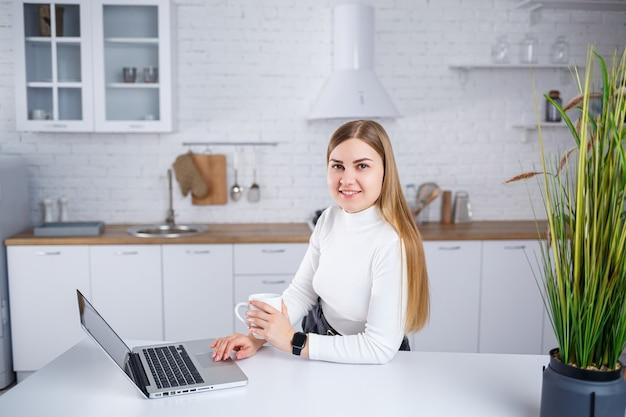 Eine schöne junge frau mit blonden haaren in einem weißen rollkragenpullover steht in einer weißen küche und arbeitet an einem laptop, sie trinkt kaffee. arbeiten sie aus der ferne von zu hause aus