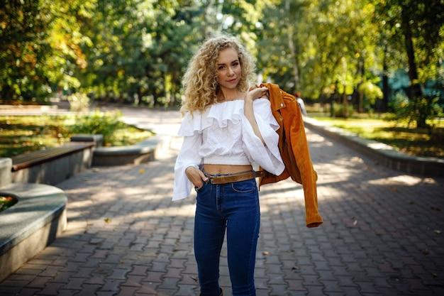 Eine schöne junge frau mit blonden locken geht durch die sonnige stadt und genießt einen mittagsspaziergang.