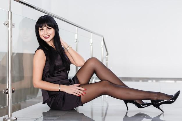 Eine schöne junge frau mit einem kurzen rock sitzt auf einem fußboden in einem weißen büro.