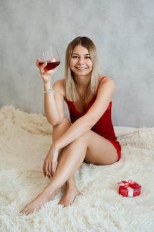 Eine schöne junge frau mit einem lächeln sitzt in roter unterwäsche auf einem weißen plaid mit wein in der hand. valentinstag morgen. vertikales foto