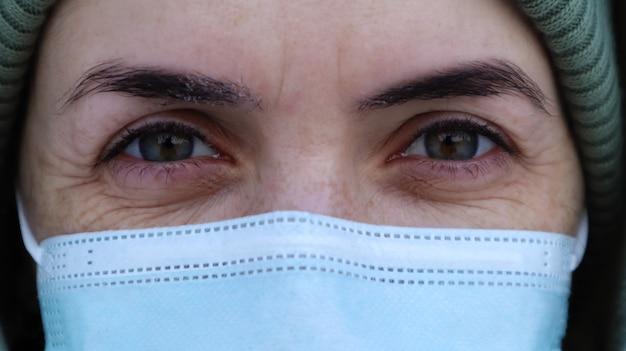 Eine schöne junge frau mit einer medizinischen maske im gesicht schaut dich in die kamera an. nahaufnahmeportrait, angst in den augen. perfekte augen. winter. coronavirus schutz. gesundheits- und sicherheitskonzept.