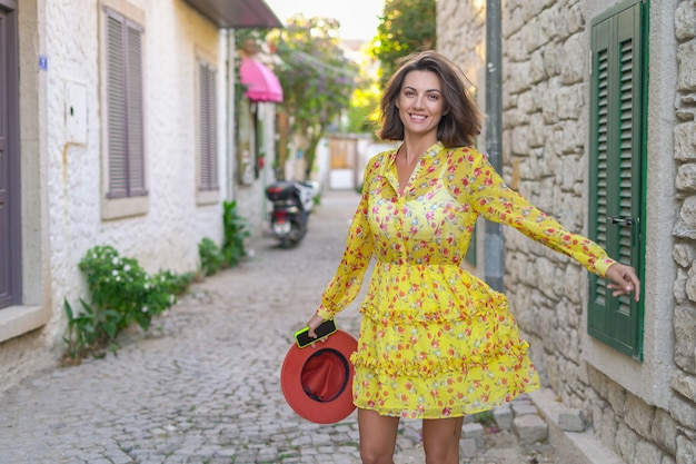 Eine schöne junge frau mit hut in einem kleid auf einer süßen, gemütlichen türkischen straße hat spaß beim gehen