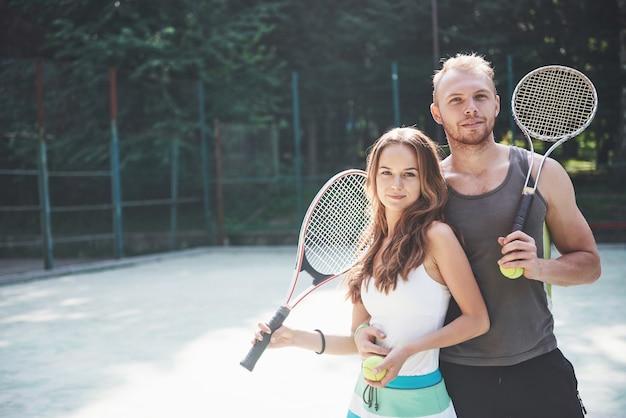 Eine schöne junge frau mit ihrem ehemann legt einen tennisplatz im freien an.