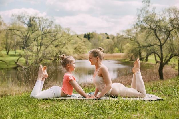 Eine schöne junge frau mit ihrer bezaubernden tochter im teenageralter praktiziert yoga im freien in einem park.